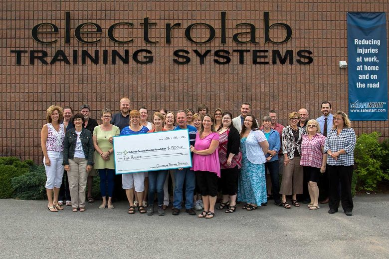 Electrolab employees holding a large check