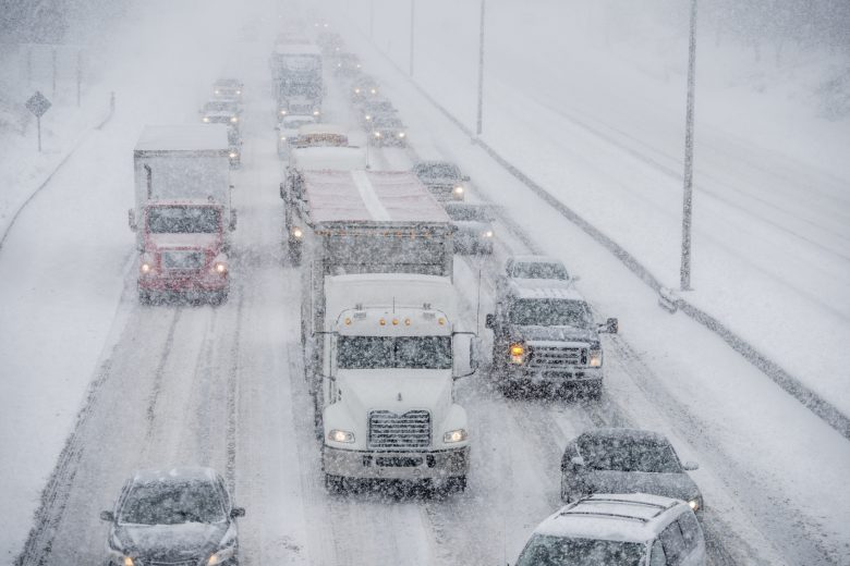 A truck drives on a crowded highway in the winter