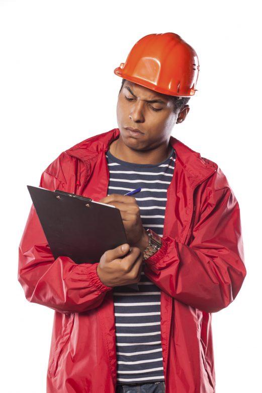 A worker wearing a hard hat writes a near-miss report