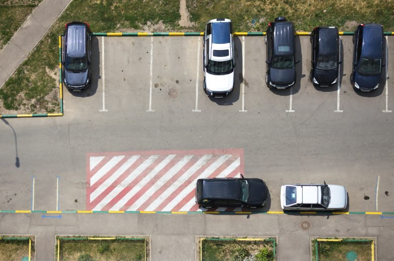 A parking lot shows several cars backed into parking spaces