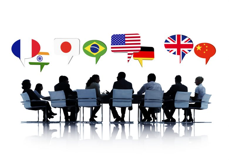 Businesspeople sit around a boardroom table speaking different languages