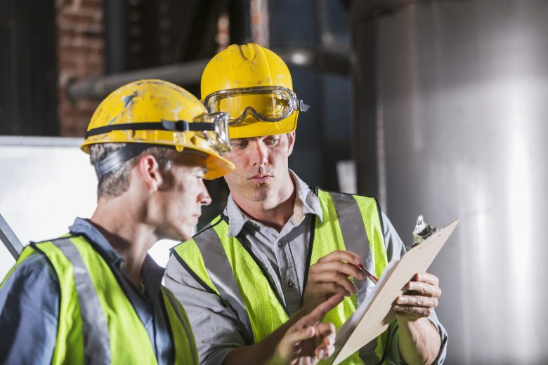 Two workers consult a safety checklist
