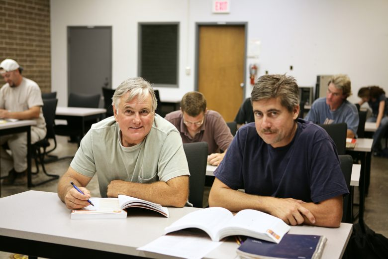 Two adult men sitting in a classroom for training