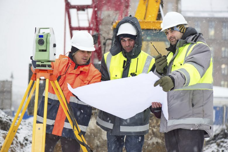Winter construction site, workers look at construction plans