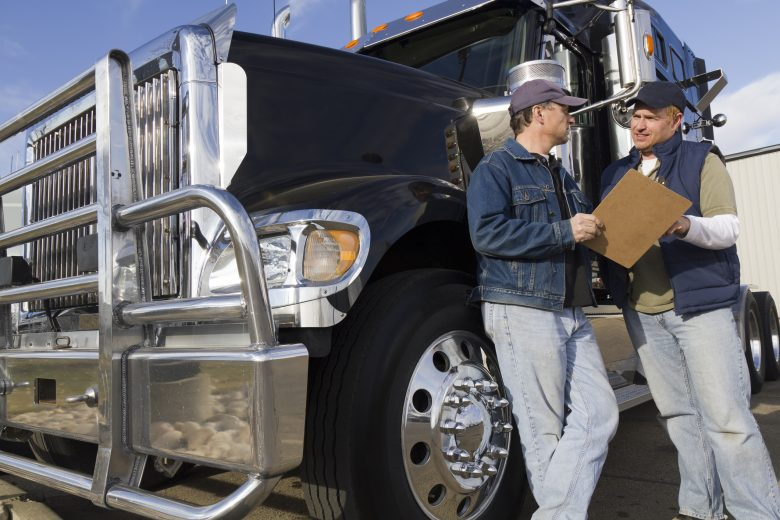 Truck drivers discussing safety outside a transport