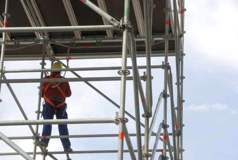 Construction worker tied off using scaffolding