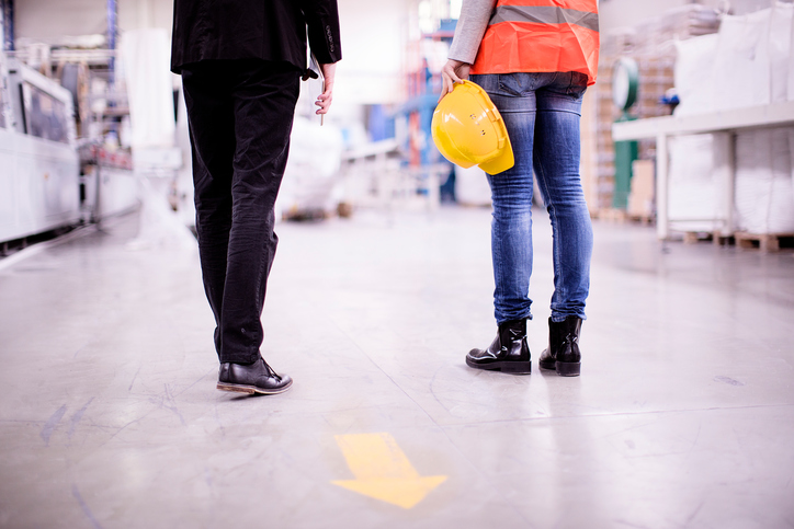 A worker holds a hard hat while standing with her supervisor to discuss safety training