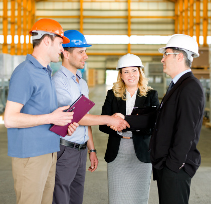 Business leaders shake hands with a safety manager