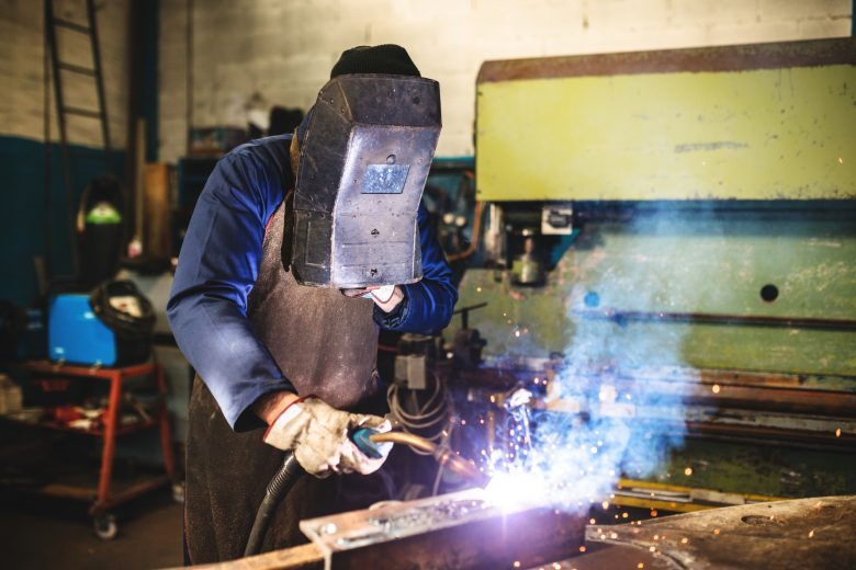 Welder in a workshop working on a piece of metal