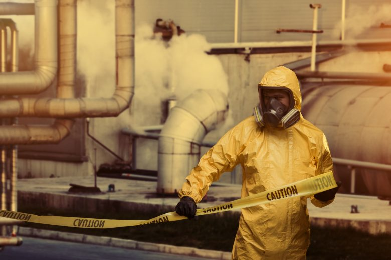Man working in a factory in protective bio hazard work wear with caution cordon tape