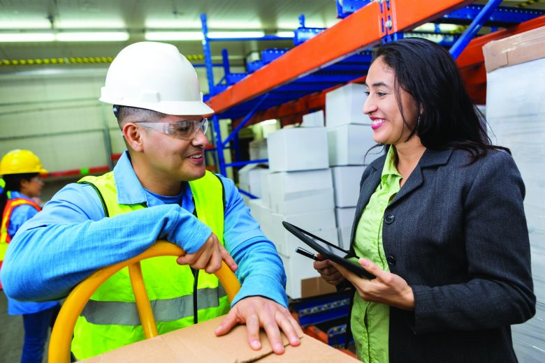 A worker and management member having a conversation in a warehouse