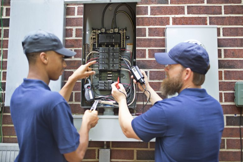 Two electricians checking an electrical panel