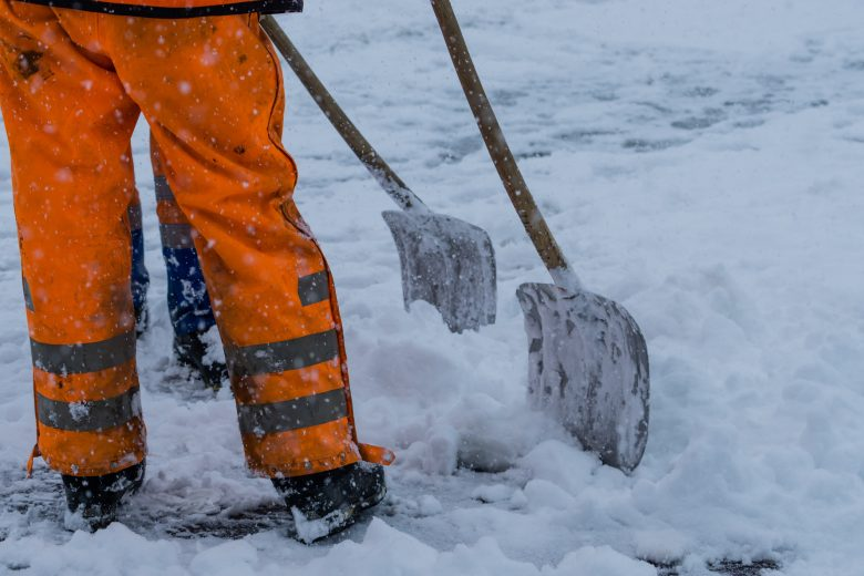 Construction workers shoveling snow