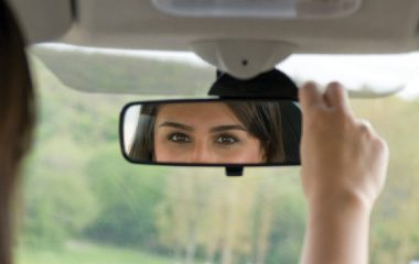Woman checking rear view mirror