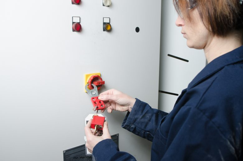 Woman performing lockout/tagout on electrical box