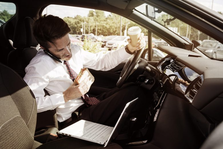 Distracted working businessman eating while on his phone and laptop driving his car