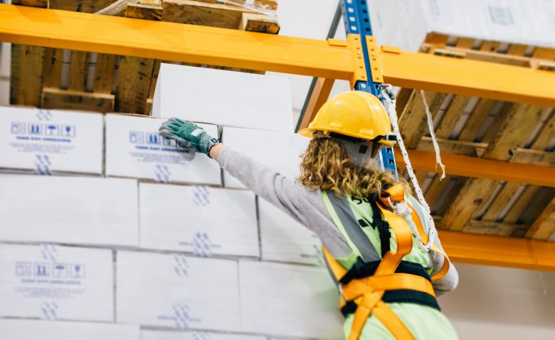 Young female manual worker hanging on a climbing rope in warehouse
