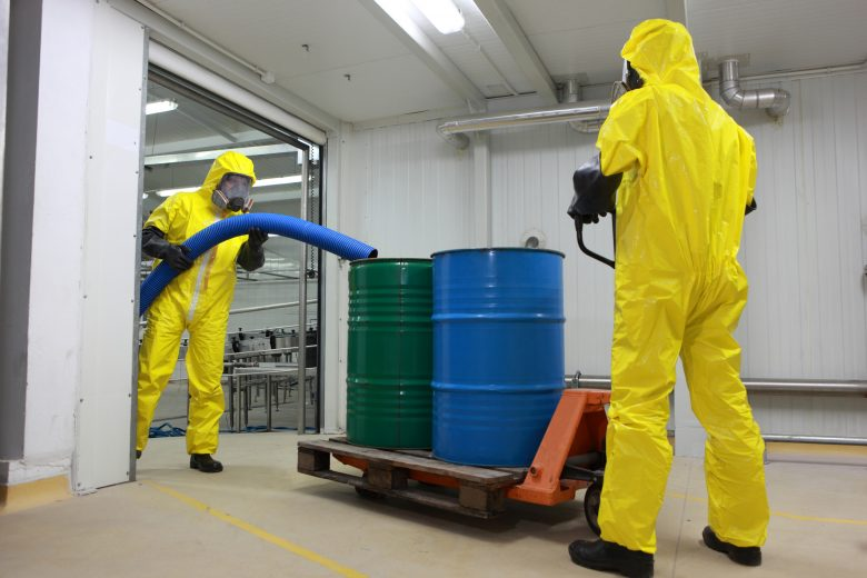 Two specialists in protective uniforms,masks,gloves and boots working with barrels of chemicals in a factory