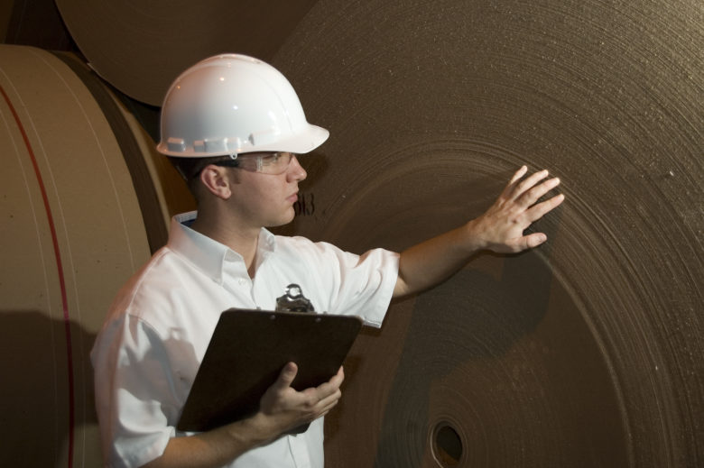 An engineer or Inspector checks a new roll of paper at a paper mill.