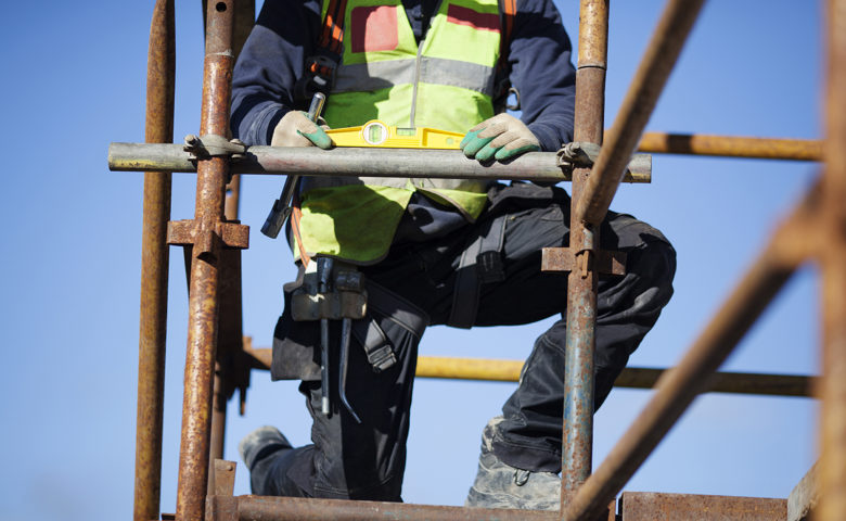 Construction worker setting up scaffolding