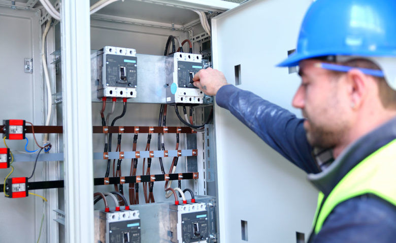 Electrician working with industrial circuit breakers