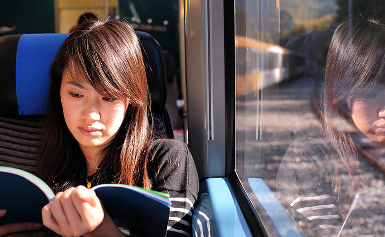 Student reading on a train