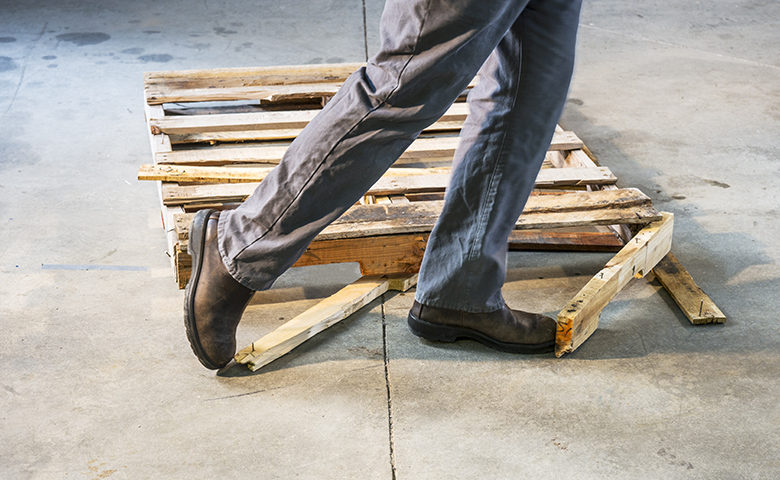Man tripping over a damaged pallet with nails sticking out of it