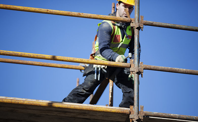 A construction worker setting up scaffolding