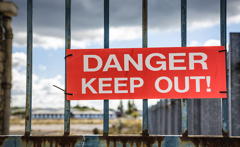 Danger keep out sign on a fence