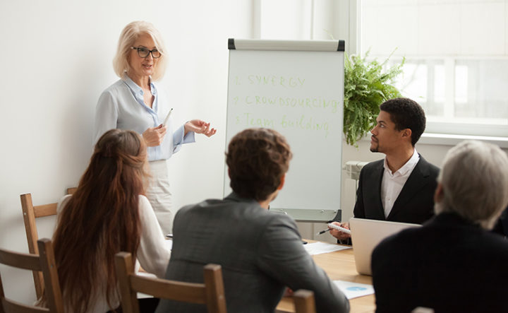 Aged attractive businesswoman giving presentation at corporate team meeting