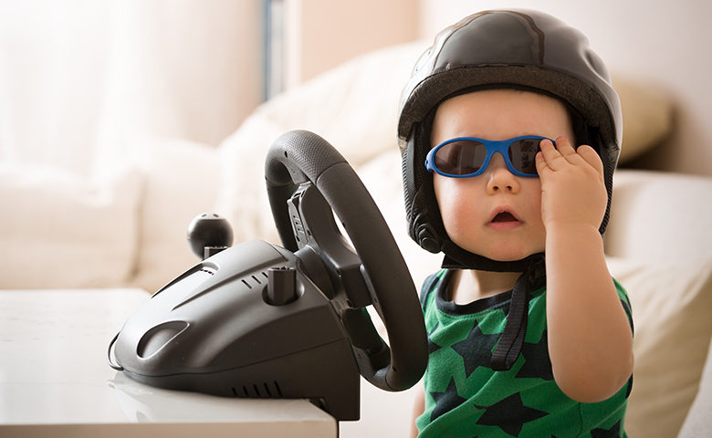 Funny picture of a baby behind the wheel with a helmet and sunglasses on.