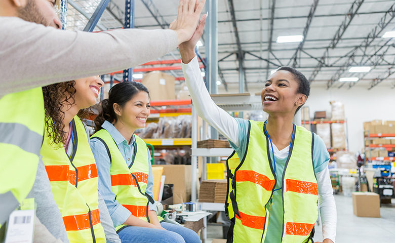Warehouse employee receives congratulations during team meeting