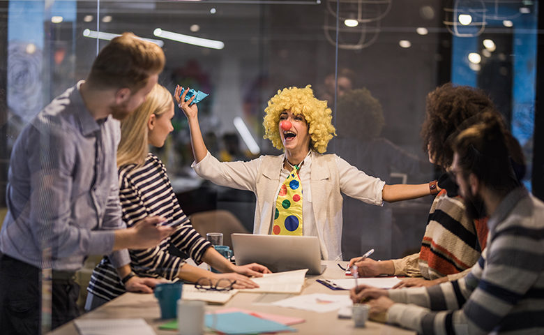 Women dressed as a clown delivering a presentation in an office