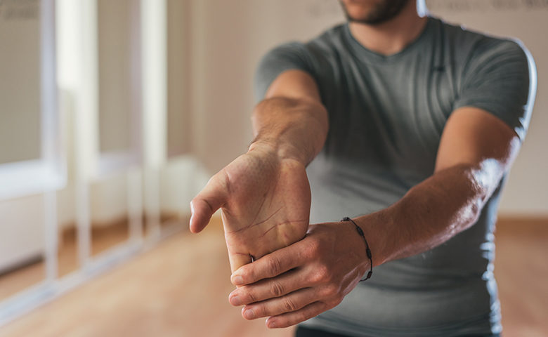 Man stretching forearm and hand