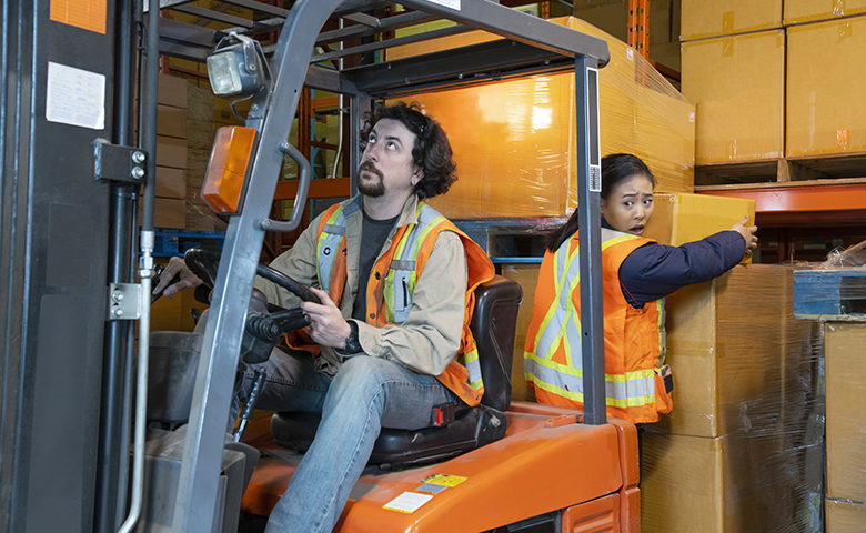 An industrial warehouse workplace safety topic. A worker in the danger zone, working behind a forklift carrying a load.