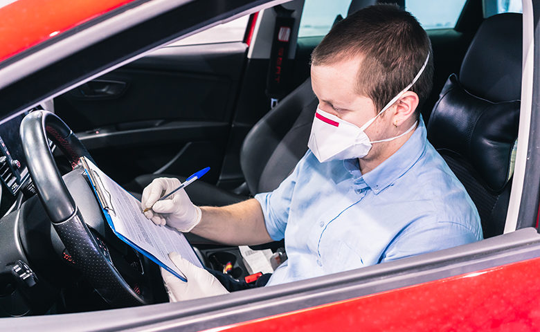 A technician doing a security inspection inside a vehicle protected with a mask and gloves to prevent the spread of virus