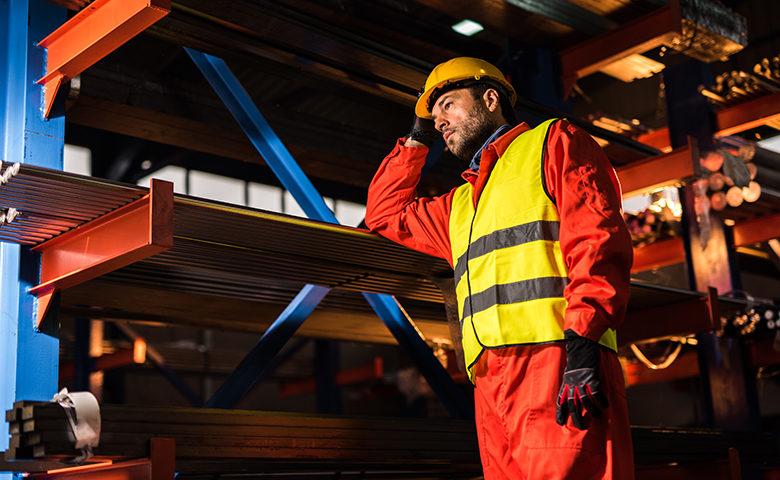 Pensive metal worker standing in aluminum mill.