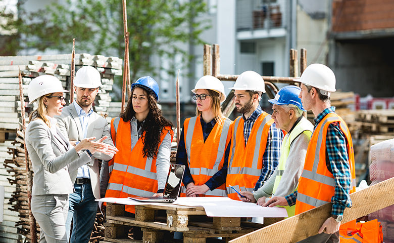 Construction workers gathered around listening to a toolbox talk