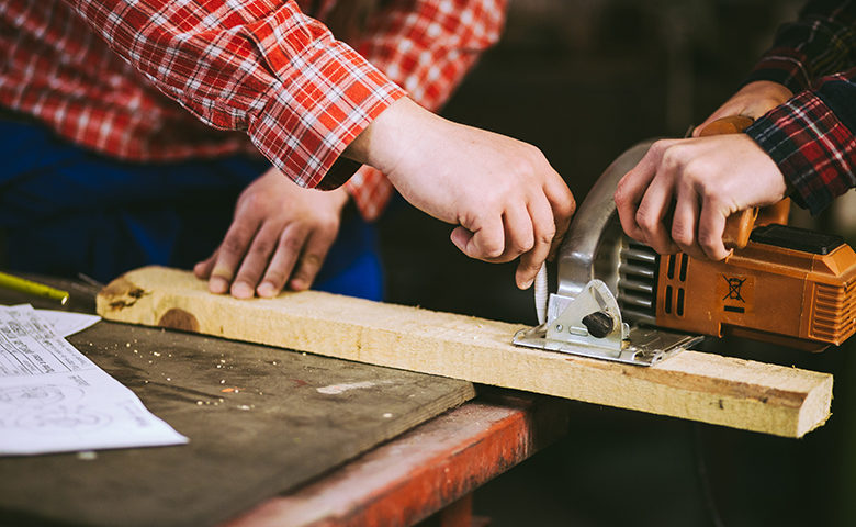Two workers using hand tools together