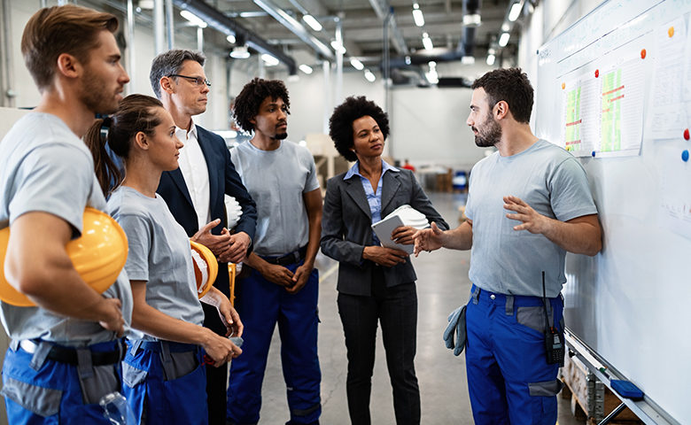 Young worker giving toolbox talk in front of whiteboard in a factory.