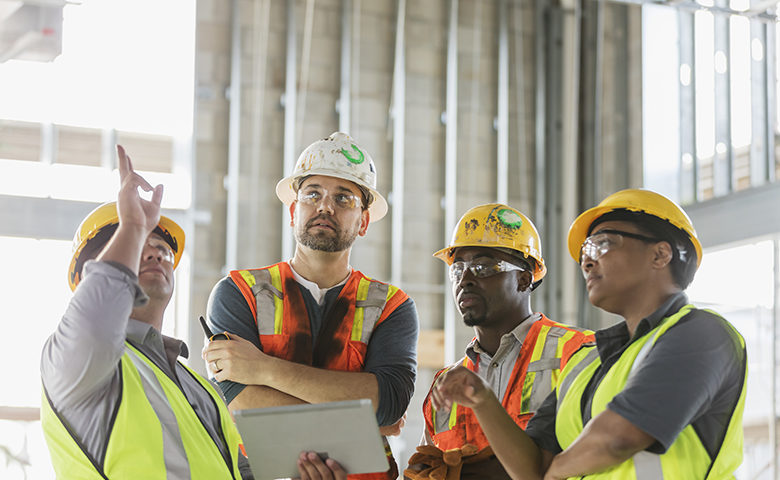 Construction workers having meeting, with digital tablet