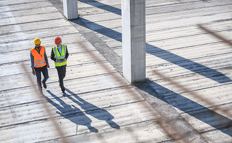 Supervisor and safety manager walking on worksite