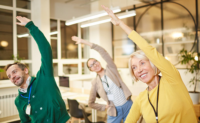 Active company employees exercising in office