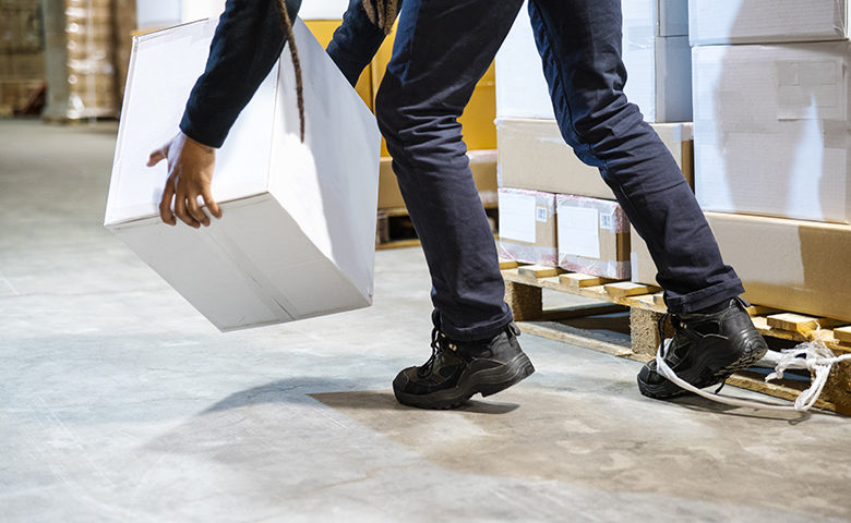 A warehouse worker tripping and falling beside a pallet