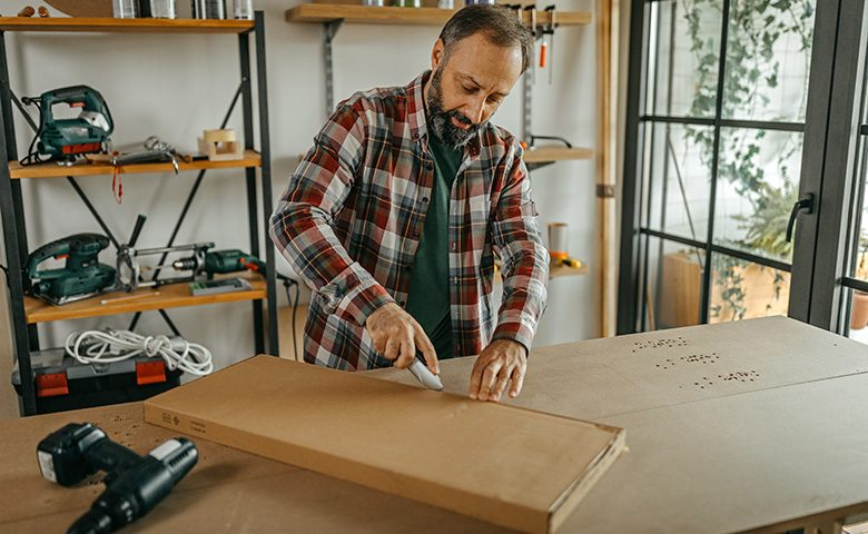 Man opening cardboard package with scalpel at home