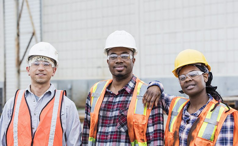 Three construction workers in hardhats and safety vests