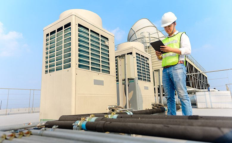 Worker doing preventive maintenance rooftop inspection