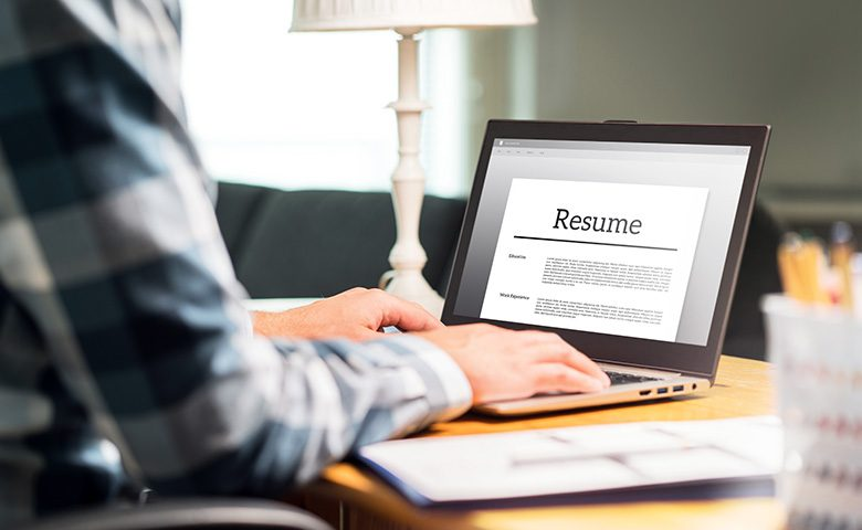Man writing resume and CV in home office.
