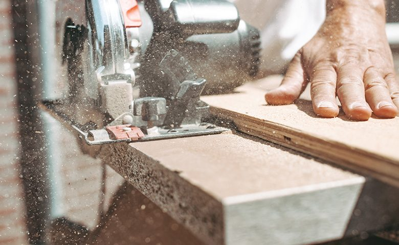 Carpenter using circular power saw for cutting wood, home improvement, do it yourself (DIY) and construction works concept, action shot